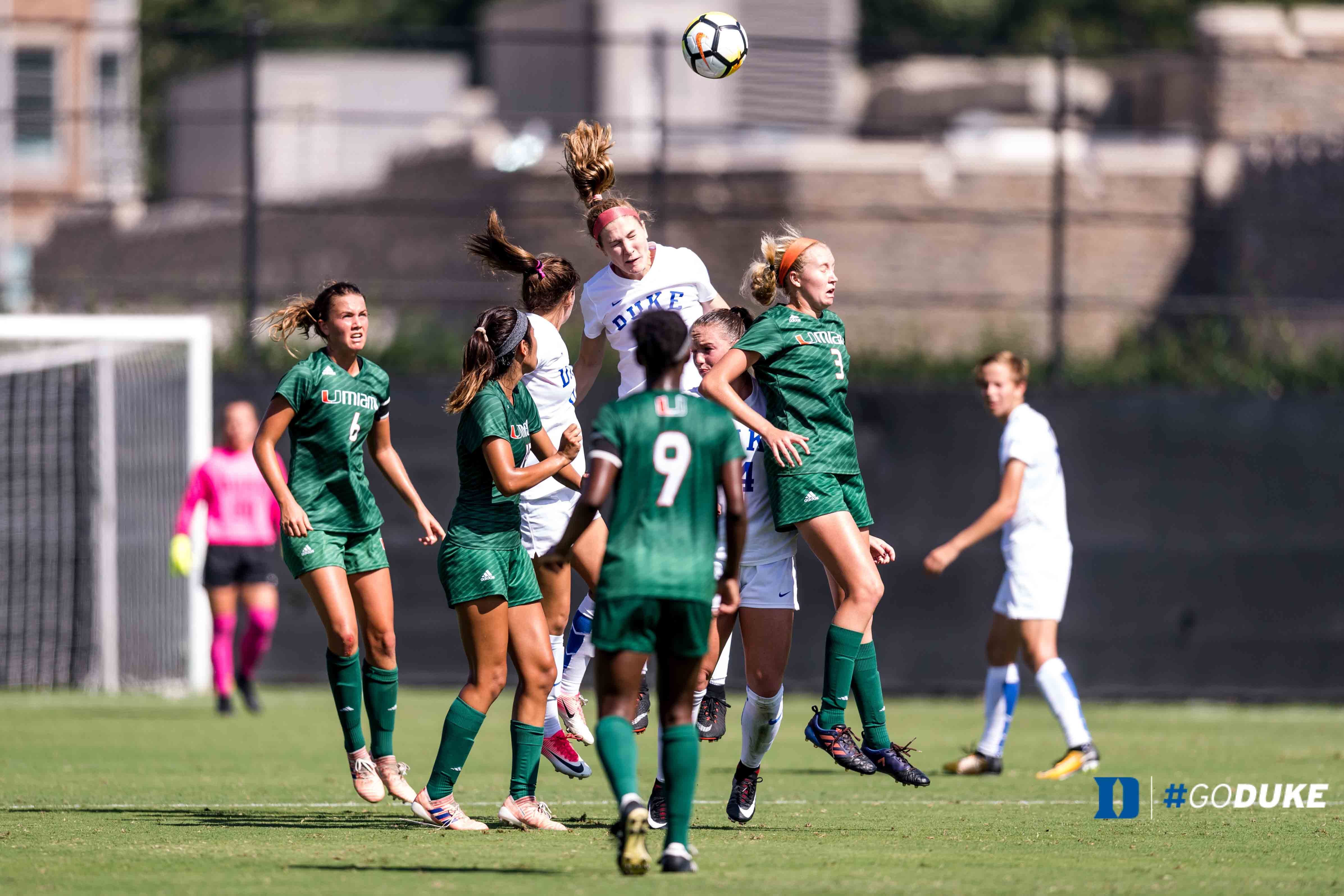 Malinda Allen going up for a header in a crowd of players.