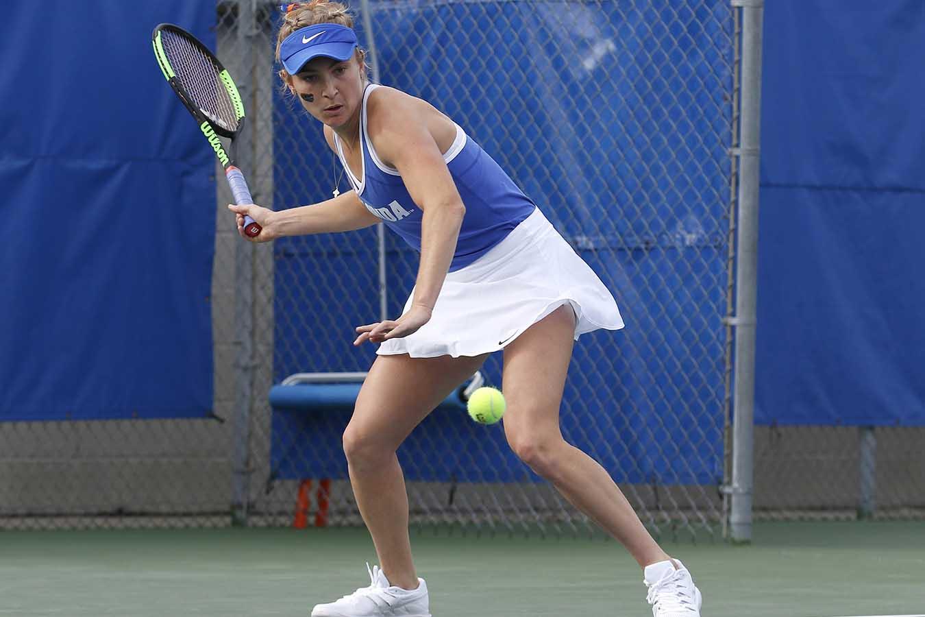 Josie Kuhlman forehand-swinging at a tennis ball.