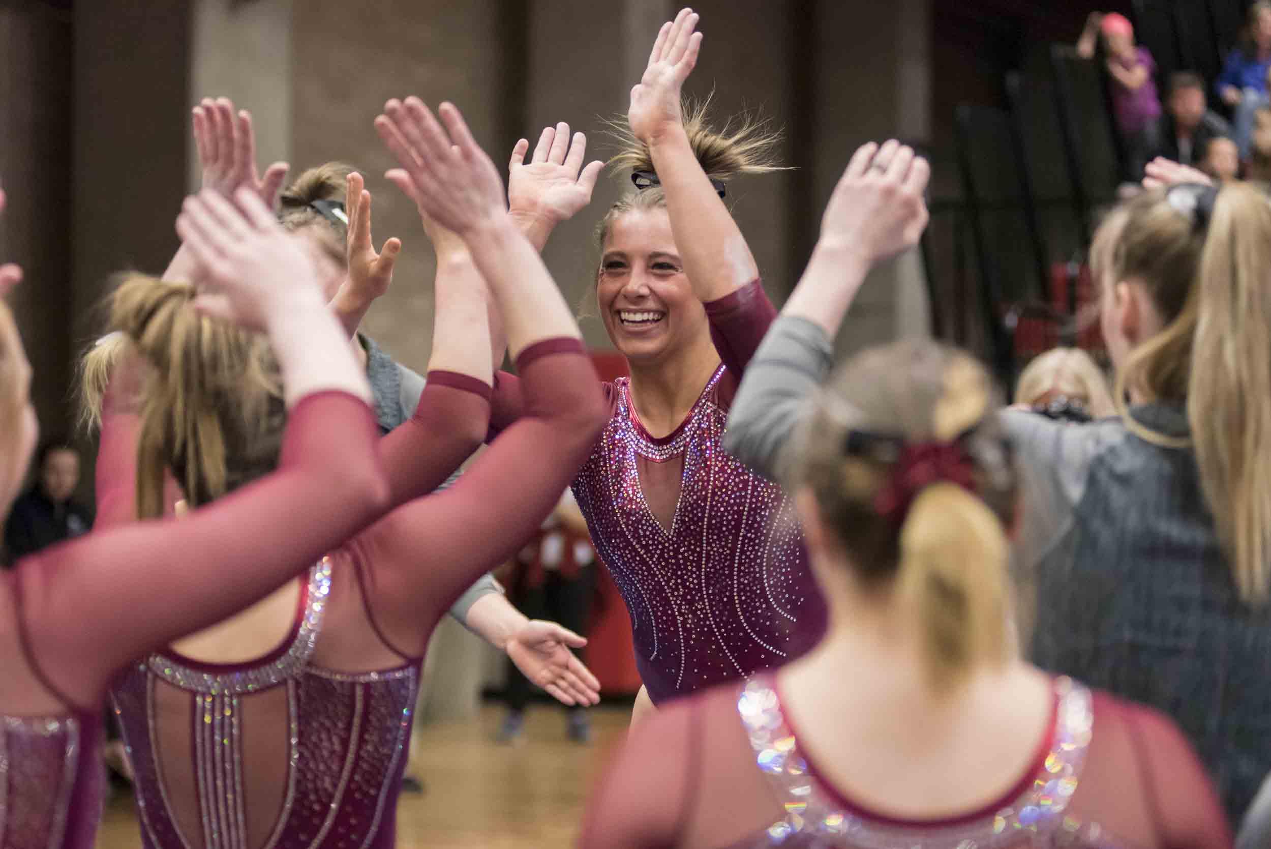 Maddie Karr high-fiving teammates following a routine.